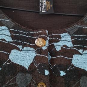 Meget flot cardigan fra Wolford i samarbejde med Vivienne Westwood. Sort/mørk brun/koksgrå/lys turkisblå. Længe ærmer, rund hals. Flot lille kant i halsen og forneden på ærmerne.  Se den også i rød. Oprindelig pris 2985.