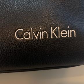 Solid Calvin Klein lædertasker.  Tasken er foret og har to store rum.  Mål: længde 40 cm brede 34 cm.  Passer perfekt til din bærbar og diverse.  Brugt ganske lidt og står stort set som ny.   Sendes hvis modtager betaler. Kan afhentes i Tjæreborg, Aarhus N eller Stilling ved Aarhus.