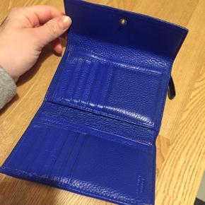 Pung i en flot blå farve med guld hardware. Udvendig og indvendig rum med lynlås og plads til kort og kontanter. Velholdt, men med brugsspor.   Np. 1000 kr. BYD!