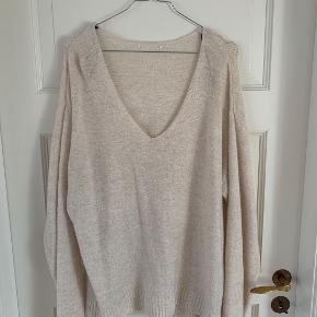 Jeg sælger denne meget fine beige strik. trøjen har en dyb v udskæring, som også fungere rigtig  fint med en t-shirt, der dermed kommer til syne i kanten.