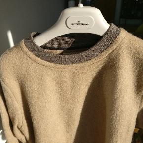 Super varm og behagelig trøje, lavet i et blandingsmateriale se sidste billede. Er i rigtig fin condition. Afslappet pasform dog med elastik i bunden. Måler ca. 67 i fuld længde, 40 fra skulder- til skuldersyning og ca. 64 fra skuldersyningen til kant