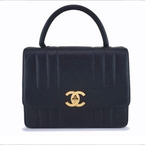 Sælger min smukke Chanel vintage kelly taske.  Denne model findes ikke mere  Men er jumbo model med xxl Chanel logo.  Np nogle lign 45.000 kr   Tasken regnes med at være før 1986 udfra serienummeret. Tasken er derfor meget unik netop pga dens årstid og facon!  Den er vintage og indeholder platina, men har sin charme stadig !❤️  Har vurderet den til 17500 kr hos Lauritz   24 karat guld på hardware modellen hedder  Følgende: Chanel Vintage Black Caviar Jumbo Kelly Flap Bag 24k   30x22 cm