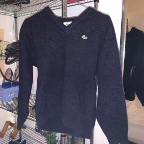 Lacoste sweater i str Small, den er lavet af 100% uld og er super dejlig. Der er et lille hul i det ene ærme, se billede 4  FRI FRAGT IDAG (11.11)