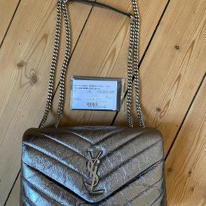 Jeg sælger min fine Saint Laurent Loulou taske Small i metallic sølv. Tasken er i god stand med enkelte slidmærker på kanten af flappen. Remmen kan bruges i to længder. Dust bag medfølger. Sætter prisen til DKK 8000,- men byd gerne.