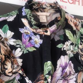 Fedeste skjorte fra H&M med print af Tiger og lilla blomster 😍 brugt men pæn. Sælges da jeg synes den er blevet for stor til mig. Str. 42. Har flæser foran og rundt om kraven samt på ærmerne. Den har nogle tråde der er blevet revet ud, både foran og på ærmet.   Bemærk - afhentes ved Harald Jensens plads eller sendes med dao. Bytter ikke 🌸  💫 Skjorte bluse hm Tiger tigre tigere mønster mønstret blomster blomstret sort lilla o