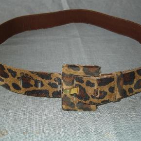 """Varetype: Bælte i """"leopard""""- plettet ruskind Størrelse: 85cm Farve: Leopardplettet  Lækkert """"leopard""""- plettet bælte i ruskind fra Kirsten Schønning i str. M, der svarer til 85 cm. i længden og bredden er 3,5 cm. Brugt ganske lidt og fremstår i flot stand. BYTTER IKKE!"""