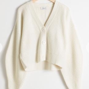 Tyk strikcardigan med flotte knapper. Er dejlig varm (50% uld)! Har desværre en fedtplet, jeg ikke kan få af - sælges derfor billigt.
