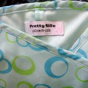 Sød foret pigekjole fra Pretty Sille i str 140. Brystvidde 35 cm, længde fra ærmegab korteste 60 cm længste 75 cm. Kjolen er i polyester