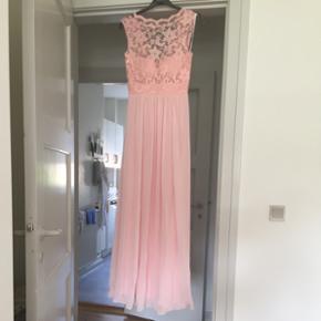 Populær rosa kjole fra Party Line  Mærket i kjolen (DFI Los Angeles) Nypris 1800 kr  Er gået ned fra 1000 kr til 500 kr som er mp. Der høre et sjal med i samme farve som kjolen. Brugt i få timer til et bryllup. Kjolen har en bette plet på det inderst lag stof af kjolen, men man ser den ikke når man har den på. Str. S. Men kan også bruges af en XS/S Tjek kommentar for hele billedet.  Sælges billigt da den ikke kan passes mere efter da jeg var gravid. (Sender ikke, skal afhentes i Aalborg Vejgaard)