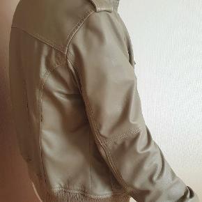 Casual jakke i det blødeste skind. Afslappet pasform. Ikke taljeret. Helforet. Brug den fx med en tyk trøje under. Army look med skulderstropper og lommer med klap og stikninger. Ribstrik ved ærmer og nedre kant gør den dejlig lun. Eneste brugsspor: En knap, der er lidt løs.  Virkelig en kvalitetsjakke, der kan holde i mange år.
