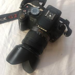 Introduced as successor to the Panasonic Lumix DMC-G1, the G2 included 720p HD video capability using both AVCHD Lite and Motion JPEG recording formats.  The G2 has a resistive touchscreen to control many camera functions including easy selection of a focus point within the live view frame. The touchscreen interface allows control duplicating the numerous dials and buttons on the G2. The G2 shipped with a new Panasonic 14–42 mm kit zoom lens, a lighter, and less expensive, version of the original Panasonic 14–45 mm kit zoom sold that shipped with the Panasonic G1.  Brugt meget lidt. Perfekt stand.