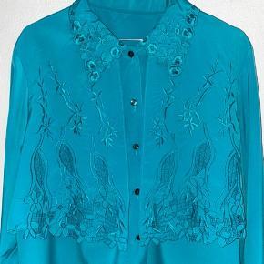 Fineste vintage blonde skjorte i turkisgrøn. Fitter onesize. Bemærk: syet et hul nederst på front, ellers fin stand. Hvis man stopper skjorten i buksen/nederdelen, ses mærket ikke.