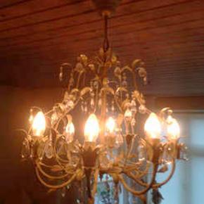 8 armet lysekrone med 110 prismer, fungerer med lysdæmper. Diameter 57 cm.