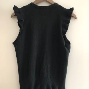 Fin vest I sort strikket lammeuld med flæser ved ærmer samt forneden.  Lille hul i flæsen forneden. Kan nemt syes.  Sælges derfor billigt.