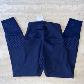 Nye med tags.  Tights fra Better Bodies har en ekstra høj talje, som kan foldes ned til en mellemhøj talje. Du får her et par tights med mange flotte detaljer, som nemt kan matches med en crop top eller en sports-BH. Waverly Mesh Tights er fremstillet i BB Gym Compression Fabric, som garanterer, at dine tights sidder godt under træningspasset. Høj talje, som kan foldes ned 7/8-længde Fugttransporterende materiale Kompression Skjult lomme i taljen Materiale: 73% Polyester, 27% Elastan.  Nypris 700
