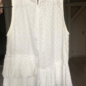 Hvid top fra i skjortelignende stof med små huller og blomsterbroderier.  Størrelsen er small, men den svarer mere til en x-small