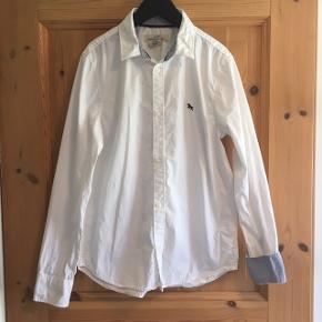 """Skjorte - hvid med mulighed for opsmøg på ærmerne med lyseblå """"denim""""."""
