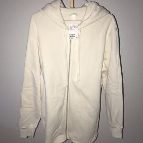 Sweatshirt-cardigan fra H&M/lang model.   - Størrelse S.  - Stadig med mærke, nypris 199.95,- - Blød indeni.  - Lang model.  - Der er noget sort på den ene af stropperne fra butikken. Jeg ved ikke hvad det er - eller om det kan komme af i vask.