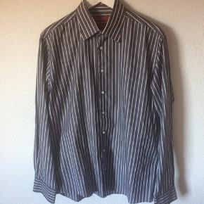 Bruun & stengade - herre skjorte Str. 42 Næsten som ny Farve: mørkegrå med hvide striber Lavet af: 100% cotton Mål: Bredde: 116 cm hele vejen rundt Længde: 78,5 cm Køber betaler Porto!  >ER ÅBEN FOR BUD<  •Se også mine andre annoncer•  BYTTER IKKE!