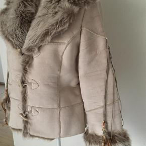 Varm jakke i imiteret skind og pels. Pynte snore med fjer og perler på ærmerne kan tages af. Længde 60. Brede 102 og Bryst 112.   Kig forbi mine annoncer 😊 Altid mængderabat  Vinter jakke med pels. Fake fur Farve: Sand