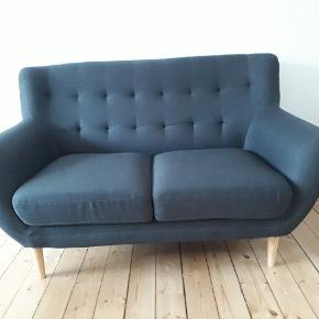 Lækker lille 2 personers sofa i retro stil. Passer perfekt ind i den lille studielejlighed. Ca. 140 cm lang og 55 i sædedybde. Fra røg- og dyrefrit hjem.  Sofaen er fra oktober af, sælges da min kæreste og jeg vil have en 3. Personers sofa efter flytning. Jeg hjælper gerne med at bære sofaen ned, men kan ikke levere. Matchende lænestol haves og sælges også evt. Denne kan muligvis godt leveres. Stolen er en smule lysere grå en sofaen. Er åben for bud i hurtig handel. Spørg for flere billeder osv.