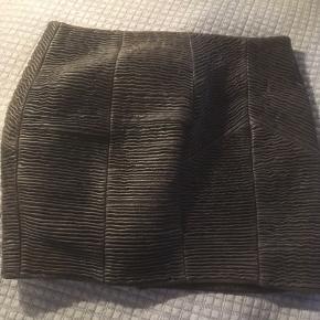 Mærke: Gestuz Størrelse: 36 Farve : gråbrun.  Længde: 38 cm og taljen er 80 cm Materiale: 100% skind. Skindet er rillet og derfor kraftig Nederdelen: foret nederdel med Lynlås bagpå. kan lynes både op og ned.. foroven og forneden. Skal sidde på hoften Stand: brugt få gange og derfor næsten som ny  Sælges 285 kr