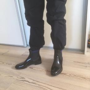 Mærke: Hecho en Espana Størrelse: 38 Farve: sort Materiale: Gummi Gummistøvlen: Smart blank gummistøvle, med sort elastik i siden og en blå kant Stand: Aldrig brugt, pga en knyste  Sælges 125 kr