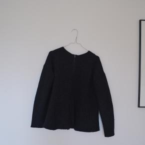 Dejlig strik fra COS. 73% uld. Mørkegrå. Lynlås i ryggen og fint snit. Har en del 'fnuller', som let kan fjernes med en fnugfjerner. Fejler ellers intet.