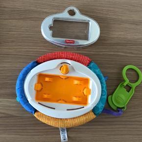 Ubrugt  Fischer-Price telefonholder til iPhone 4. Holderen har blød og farverig polstring som barnet kan holde i. Derudover har den en hank og klips så den kan sættes fast i barnevogn/klapvogn, så hvis barnet smider den overboer sikre hanken at den ikke falder på jorden. Holderen har desuden en fod, så den nemt kan anvendes på en restaurant til tegnefilm uden at barnet får hold i nakken af at kigge ned. Fra dyrefrit, røgfrit og parfumefrit hjem