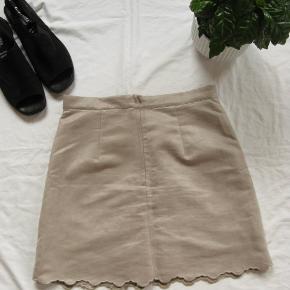 Skøn nederdel i ruskindslook.  Størrelsen er en 40, men som det fremgår af målene, er den lille i størrelsen.  Livvidde ca.78,5 cm. Længde ca. 44 og 46cm.  Jeg tager desværre ikke billeder med tøjet på.