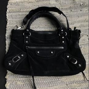 Jeg sælger min Balenciaga First taske i sort ruskind, da jeg ikke får den brugt. Det er perfekt taske til byen eller lignende 😊 Tasken er i flot stand og fejler stort set intet - dog har jeg spildt en smule klar neglelak i det inderste, lille rum, men det betyder intet for brug (se venligst billede). JEG BYTTER IKKE