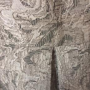 Adolfo Dominduez - nederdel Str. 44 Næsten som ny Farve: sølv/guld mønstret Lavet af: 100% polyester For: 100% acetate Mål: Livvidde: 88 cm hele vejen rundt Længde: 52 cm Køber betaler Porto!  >ER ÅBEN FOR BUD<  •Se også mine andre annoncer•  BYTTER IKKE!