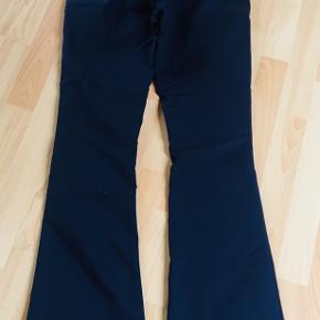 Mørkeblå/navy lavtaljede, flared bukser med lommer i siden. Brugt få gange - ingen synlige skader eller slid. Mål: Linning: 37 cm Indersøm: 80 cm