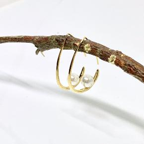 Ny dråbeformet messing ørering som er belagt med ægte forgyldning. Heri en enkel shell perle.  Ørebøjlen måler ca. 37x26 mm  Kan sendes for 10,- som brev