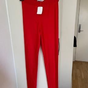 Røde lidt shiny leggings fra UO (light before Dark kollektion) i str XS. Totallængde ca 100 cm og benlængde målt på indersiden ca 76-77 cm. Bredde i taljekant kan stretches til ca 42,5-43 cm. Materiale nylon med 10% stretch. Sælges for halv pris plus porto