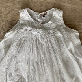 Let og fin sommerkjole - helt hvid. Materialet er bomuld og der er for, så den er ikke gennemsigtig