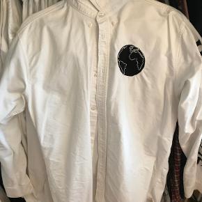 Hvid skjorte med print på ærmerne (Space For Everyone) fra danske Soulland. Skjorten er anvendt få gange, og fremstår derfor næsten som ny. Skjorten er regular fit, og af Oxford kvalitet.