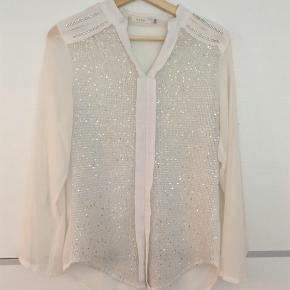 Sød semi-gennemsigtig skjorte med palietter. Den har lange ærmer, men har knapper så den kan rulles op til kortere ærmer.