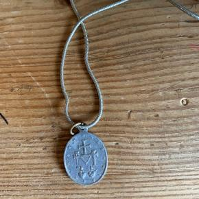 Fin sølvhalskæde fra genbrug. Vedhænget har symboler på begge sider, den ene med et afbillede af jomfru Maria og den anden med noget der ligner et våbentegn.