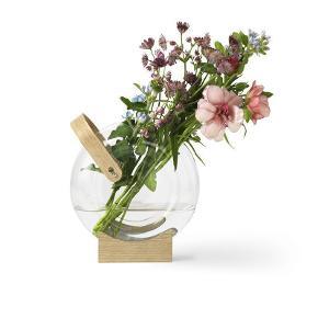 Brand: Mater Varetype: vase Størrelse: 18 x 20 cm Farve: glas og træ Oprindelig købspris: 795 kr. Prisen angivet er inklusiv forsendelse.  Aldrig brugt - levers i original emballage. Handle Vase er designet af den danske arkitekt Eva Harlou.     Vasen er håndblæst i borosilicatglas og hviler elegant på en fod af FSC certificeret egetræ, der gør det muligt at lege med positionering af blomsterne. Håndtaget giver desuden vasen mulighed for at hænge i skærme og dekorative opsætninger.    Materialer  Borosilicatglas  FSC certificeret egetræhåndtag og blok med gennemsigtige silikone propper    Kapacitet  1700 ml | 57.4 oz     Dimensioner  Højde 18 cm x Bredde 20 cm x Dybde 7.5 cm