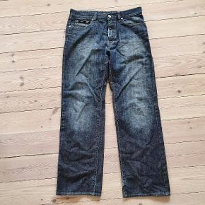 Blå jeans fra Hugo Boss i str 32/30. Bukserne er brugte men ellers i fin stand. Eneste skade er i hælområderne hvor de er trådt lidt i stykker - kan ses på det ene billede.