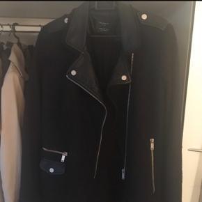 """#30dayssellout Jeg sælger denne fede Zara frakke i sort med læderlignende detaljer samt uld design. Kan tjekke om det er ægte uld hvis der er interesse for det. Det er en str M men den er lille i størrelsen, så den vil formentlig være bedre til en str S. og derfor har jeg sat den til denne størrelse.   Jeg byttede mig til den herinde på Tradono men da den er for lille til mig, sælges den videre. Ejeren før mig havde brugt den en del og der er slid at se, det man kan se på sidste billede i nakken/ved mærkatet, der er noget af materialet skallet af men det er ikke rigtig noget man vil kunne lægge mærke til da det jo som sagt er i nakken og ellers er der ikke noget slid men altså derfor er standen sat som """"Slidt"""". Frakken har været til rens, så den er helt fri for røg lugt og er ellers en rigtig fin frakke der sælges billigt som man kan se pga. det omtalte slid i nakken.  Hvis den skal sendes, betaler køber fragt.  Mvh Betina Thy"""