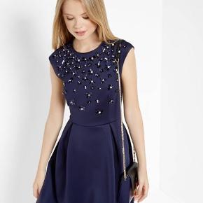 Virkelig fin mørkeblå Ted Baker kjole i XS / 34 / størrelse UK 0. Den har de fineste blå blomster lavet af palietter og sten der glimter flot i lyset.  Jeg får den desværre ikke brugt og det er jo synd, hvorfor jeg nu sælger den.
