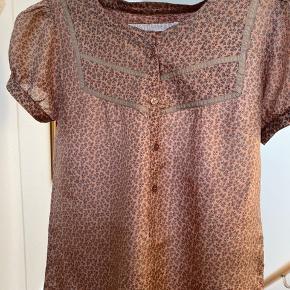 Virkelig sød silketop fra Custommade. 100% silke. Farven er lys ler med små freskenfarvede blomster. Ingen tegn på slid. Rigtig søde ærmer. Brugt få gange