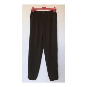 Enkle bukser med elastisk talje og bånd langs siderne. Er taget i brug en enkelt gang eller to - standen er derfor lig ny. Sammensætningen består af polyester. Org. pris: 349 kr.  Mp: se prisen + evt. porto