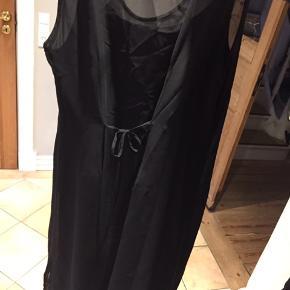 Fin sort kjole i to lag som er syet sammen fra under armene og ned. Slids i begge sider og bindebånd bagpå. Perfekt til nytåret🎉🍾🥂