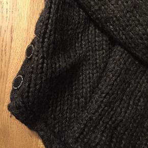 """Fin rullekrave / strik i alpaca uld blanding. Trøjen er mørkegrå med fine detaljer, lidt længere bagtil end foran og med """"logo"""" knapper i siden og ved halsen. Kraven kan knappes op. Rigtig fin kvalitet, der ikke fnugger."""