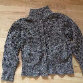 Grålig/ / brun strik med krave i rib og to lommer foran sælges. Længde 59 cm. Materiale 50 % acryl, 15 % mohair, 18 % uld og 17 % nylon.