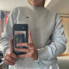 Sælger min grå Champion sweatshirt. Det er en herremodel S, men passer en pige S/M.  Brugt meget få gange og står derfor næsten som ny.  Køber betaler fragt