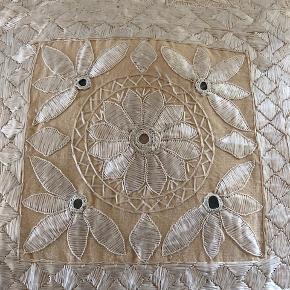 Pyntepude. Sølvhvid på lys beige baggrund., Zenza  Skøn og virkelig smuk pude i linnen i klassisk Zenza -stil. Puden er håndlavet i egypten.  Farve er hvid/sølvhvid på en baggrund af lys beige.  Mærke: Zenza Størrelse: Ca 42 x 40 cm  Zenza kombinerer gamle teknikker med et moderne twist i deres design og udvikler en meget elegant, intim men alligevel moderne atmosfære.  Nypris: 45 EUR = ca. 330 kr  Købt i Holland. Ca 2.5 år gammel. Ligget i sofa - og brugt ind imellem. Fremstår pænt.